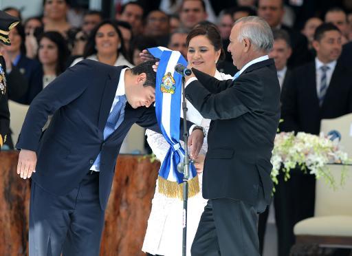 New Honduran President Juan Orlando Hernandez (L), accompanied by his wife Ana Garcia, receives the presidential sash from Congress prersident Mauricio Oliva, during his inauguration on January 27, 2014. (AFP/Orlando Sierra)