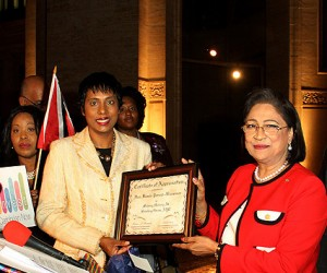 Invest Caribbean Now Founder/Chairman Felicia Persaud, l, presents a certificate of appreciation to Trinidad & Tobago Prime Minister Kamla Persad-Bissessar as ICN President Sheila Newton-Moses, far left, looks on. (Hayden Roger Celestin image)