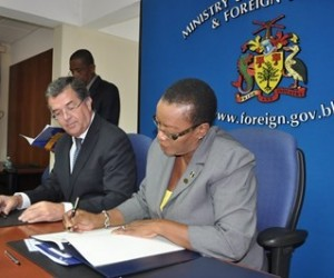 Minister of Foreign Affairs and Foreign Trade, Senator Maxine McClean signing the MOU while Canada's High Commissioner to Barbados, Richard Hanley, looks on. (A.Miller/BGIS)