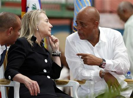 Former U.S. Secretary of State Hillary Clinton speaks with Haitian President Michel Martelly (R).