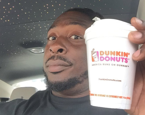 ricky-jean-francois-poses-with-a-dunkin-donuts-coffee