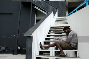 > on December 7, 2017 in St JA displaced resident from the island of Barbuda checks his phone at a shelter at a cricket stadium on December 7, 2017 in St John's, Antiqua. Barbudaohn's, [COUNTRY].