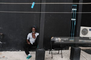 A displaced resident from the island of Barbuda sits inside a shelter at a cricket stadium on December 7, 2017 in St John's, Antiqua. Barbuda