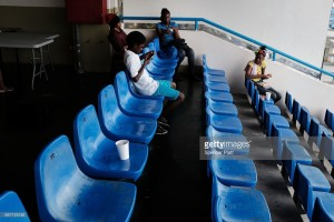 Displaced residents from the island of Barbuda sit inside a shelter at a cricket stadium on December 7, 2017 in St John's, Antigua.